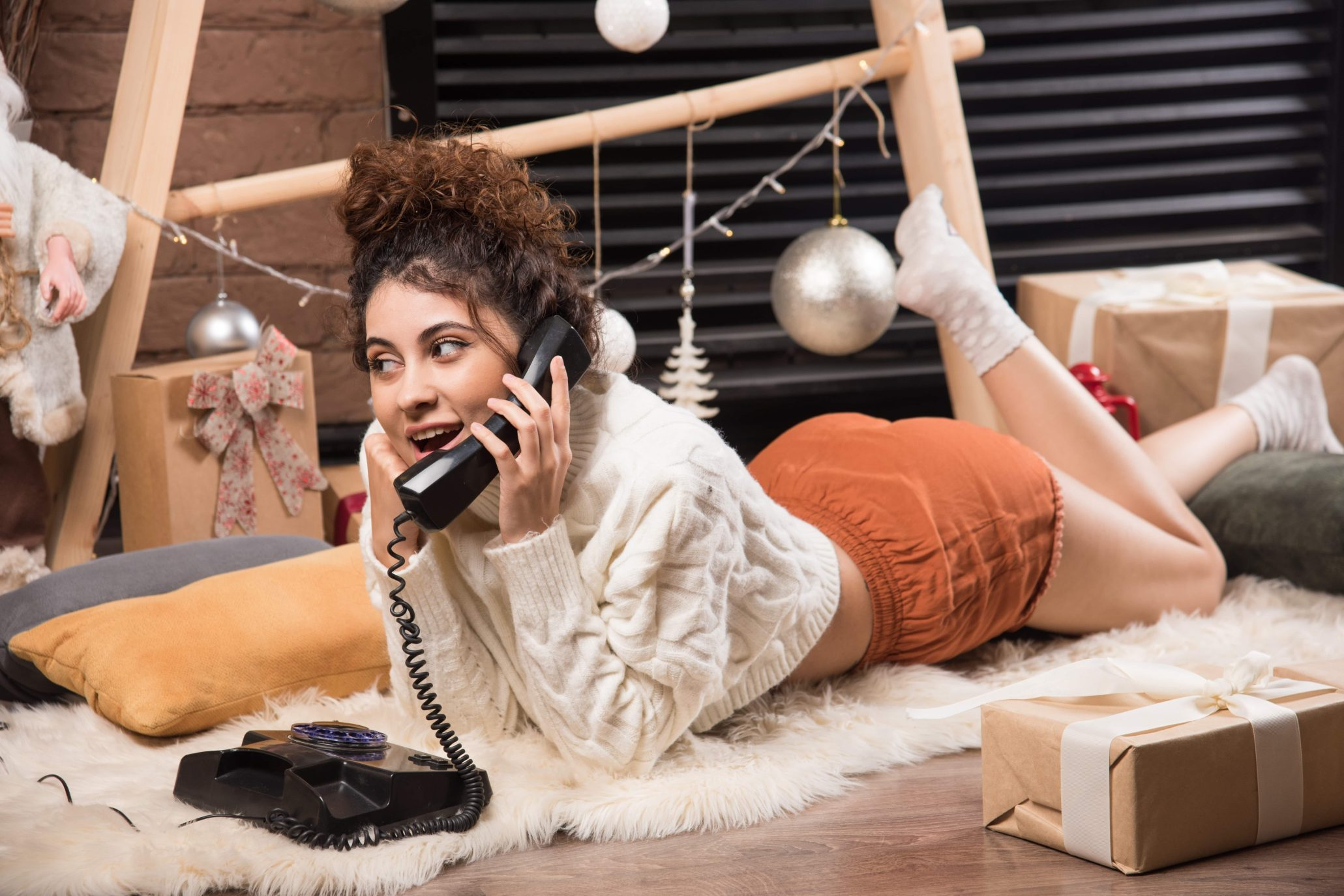 young women lying on the floor speaking on a home telephone